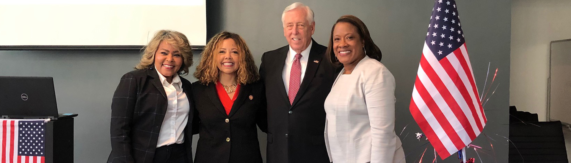 Hoyer standing with other professionally dressed women by an American flag